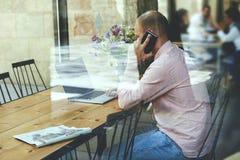 Νέος επιχειρηματίας που έχει το μεσημεριανό γεύμα σε ένα εστιατόριο και που μιλά στο τηλέφωνο που λύνει τα επιχειρησιακά ζητήματα Στοκ Φωτογραφίες
