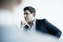 Νέος επιχειρηματίας που ακούει σε μια επιχειρησιακή συνεδρίαση Στοκ Εικόνα