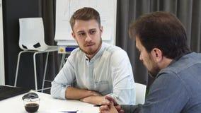 Νέος επιχειρηματίας που ακούει τον ώριμο συνάδελφό του κατά τη διάρκεια της συνεδρίασης απόθεμα βίντεο