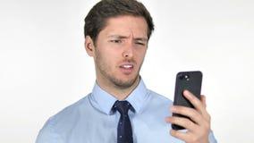 Νέος επιχειρηματίας που αντιδρά στην απώλεια σε Smartphone στο άσπρο υπόβαθρο απόθεμα βίντεο