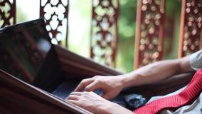 Νέος επιχειρηματίας που βρίσκεται σε μια αιώρα και που εργάζεται σε ένα lap-top 1920x1080 απόθεμα βίντεο