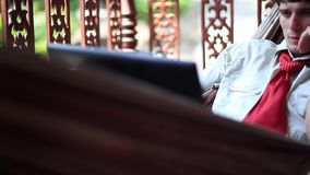 Νέος επιχειρηματίας που βρίσκεται σε μια αιώρα και που εργάζεται σε ένα lap-top 1920x1080 φιλμ μικρού μήκους