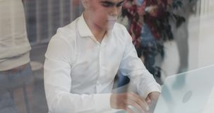 Νέος επιχειρηματίας που γράφει κάτω τις επιχειρησιακές πληροφορίες στο σημειωματάριό του εξετάζοντας το lap-top στον υαλώδη καφέ  απόθεμα βίντεο