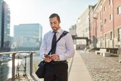 Νέος επιχειρηματίας που δακτυλογραφεί SMS στο smartphone Στοκ Εικόνα