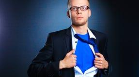 Νέος επιχειρηματίας που ενεργεί όπως έναν έξοχο ήρωα και λυσσασμένος το πουκάμισό του, που απομονώνεται στο γκρίζο υπόβαθρο Στοκ Φωτογραφία