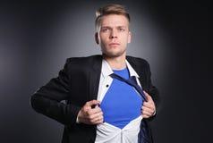 Νέος επιχειρηματίας που ενεργεί όπως έναν έξοχο ήρωα και λυσσασμένος το πουκάμισό του, που απομονώνεται στο γκρίζο υπόβαθρο Νέος  Στοκ εικόνα με δικαίωμα ελεύθερης χρήσης