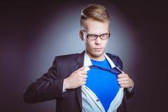 Νέος επιχειρηματίας που ενεργεί όπως έναν έξοχο ήρωα και λυσσασμένος το πουκάμισό του, που απομονώνεται στο γκρίζο υπόβαθρο Νέος  Στοκ φωτογραφία με δικαίωμα ελεύθερης χρήσης