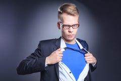 Νέος επιχειρηματίας που ενεργεί όπως έναν έξοχο ήρωα και λυσσασμένος το πουκάμισό του, που απομονώνεται στο γκρίζο υπόβαθρο Νέος  Στοκ Εικόνα