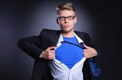 Νέος επιχειρηματίας που ενεργεί όπως έναν έξοχο ήρωα και λυσσασμένος το πουκάμισό του, στο γκρίζο υπόβαθρο Νέος επιχειρηματίας Στοκ Εικόνες
