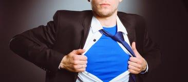 Νέος επιχειρηματίας που ενεργεί όπως έναν έξοχο ήρωα και λυσσασμένος το πουκάμισό του, που απομονώνεται στο γκρίζο υπόβαθρο Στοκ Εικόνα