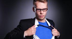 Νέος επιχειρηματίας που ενεργεί όπως έναν έξοχο ήρωα και λυσσασμένος το πουκάμισό του, στο γκρίζο υπόβαθρο Στοκ Εικόνες