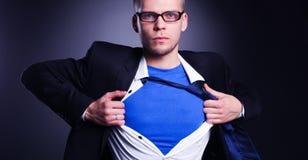 Νέος επιχειρηματίας που ενεργεί όπως έναν έξοχο ήρωα και λυσσασμένος το πουκάμισό του, στο γκρίζο υπόβαθρο Στοκ φωτογραφία με δικαίωμα ελεύθερης χρήσης