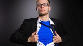Νέος επιχειρηματίας που ενεργεί όπως έναν έξοχο ήρωα και λυσσασμένος το πουκάμισό του, στο γκρίζο υπόβαθρο Στοκ Φωτογραφίες