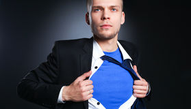 Νέος επιχειρηματίας που ενεργεί όπως έναν έξοχο ήρωα και λυσσασμένος το πουκάμισό του, που απομονώνεται στο γκρίζο υπόβαθρο Στοκ εικόνα με δικαίωμα ελεύθερης χρήσης