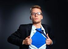 Νέος επιχειρηματίας που ενεργεί όπως έναν έξοχο ήρωα και λυσσασμένος το πουκάμισό του, που απομονώνεται στο γκρίζο υπόβαθρο Στοκ εικόνες με δικαίωμα ελεύθερης χρήσης