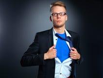 Νέος επιχειρηματίας που ενεργεί όπως έναν έξοχο ήρωα και λυσσασμένος το πουκάμισό του, που απομονώνεται στο γκρίζο υπόβαθρο Στοκ φωτογραφίες με δικαίωμα ελεύθερης χρήσης