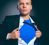 Νέος επιχειρηματίας που ενεργεί όπως έναν έξοχο ήρωα και λυσσασμένος το πουκάμισό του, που απομονώνεται στο γκρίζο υπόβαθρο Στοκ Εικόνες
