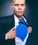 Νέος επιχειρηματίας που ενεργεί όπως έναν έξοχο ήρωα και λυσσασμένος το πουκάμισό του, στο γκρίζο υπόβαθρο Στοκ εικόνα με δικαίωμα ελεύθερης χρήσης
