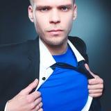 Νέος επιχειρηματίας που ενεργεί όπως έναν έξοχο ήρωα και λυσσασμένος το πουκάμισό του, που απομονώνεται στο γκρίζο υπόβαθρο Στοκ Φωτογραφίες