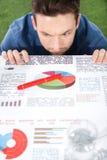 Νέος επιχειρηματίας που εξετάζει τα έγγραφα με τα επιχειρησιακά διαγράμματα και τα διαγράμματα Στοκ Εικόνα