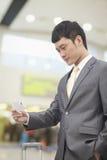 Νέος επιχειρηματίας που εξετάζει το εισιτήριο πτήσης του στον αερολιμένα Στοκ Εικόνες