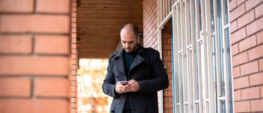 Νέος επιχειρηματίας που εξετάζει το τηλέφωνο κυττάρων του Στοκ Φωτογραφία