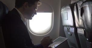 Νέος επιχειρηματίας που εργάζεται με το μαξιλάρι στο αεροπλάνο απόθεμα βίντεο
