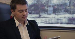 Νέος επιχειρηματίας που εργάζεται με το μαξιλάρι στο τραίνο απόθεμα βίντεο