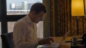 Νέος επιχειρηματίας που εργάζεται με το lap-top και φιλμ μικρού μήκους