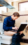 Νέος επιχειρηματίας που εργάζεται στην τουαλέτα με το lap-top Στοκ Φωτογραφίες