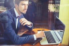 Νέος επιχειρηματίας που εργάζεται στον καφέ, που χρησιμοποιεί το lap-top Στοκ Εικόνες