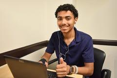 Νέος επιχειρηματίας που εργάζεται στο lap-top με τους αντίχειρες επάνω στοκ φωτογραφία