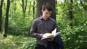 Νέος επιχειρηματίας που διαβάζει ένα βιβλίο στα ξύλα κοντά σε ένα δέντρο φιλμ μικρού μήκους