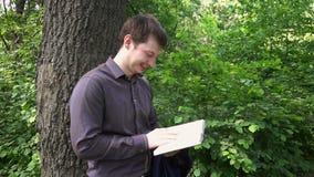 Νέος επιχειρηματίας που διαβάζει ένα βιβλίο στα ξύλα κοντά σε ένα δέντρο απόθεμα βίντεο
