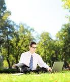 Νέος επιχειρηματίας που κάθεται εργασία σε ένα lap-top και γράψιμο κάτω του αριθ. Στοκ Εικόνα