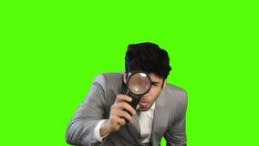 Νέος επιχειρηματίας που κοιτάζει μέσω μιας ενίσχυσης - γυαλί στο πράσινο υπόβαθρο φιλμ μικρού μήκους