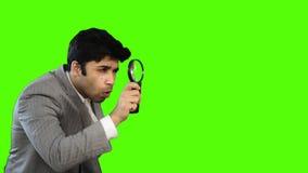 Νέος επιχειρηματίας που κοιτάζει μέσω μιας ενίσχυσης - γυαλί στο πράσινο υπόβαθρο απόθεμα βίντεο