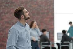 Νέος επιχειρηματίας που κοιτάζει μακριά εργαζόμενος στο γραφείο Στοκ εικόνες με δικαίωμα ελεύθερης χρήσης