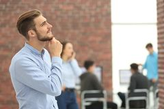 Νέος επιχειρηματίας που κοιτάζει μακριά εργαζόμενος στο γραφείο Στοκ εικόνα με δικαίωμα ελεύθερης χρήσης