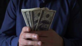 Νέος επιχειρηματίας που κρατά έναν ανεμιστήρα των λογαριασμών εκατό δολαρίων φιλμ μικρού μήκους