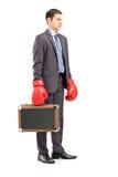 0 νέος επιχειρηματίας που κρατά έναν χαρτοφύλακα με τα εγκιβωτίζοντας γάντια Στοκ Εικόνα