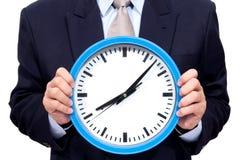 Νέος επιχειρηματίας που κρατά ένα ρολόι Στοκ Φωτογραφία