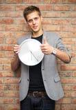 Νέος επιχειρηματίας που κρατά ένα ρολόι και που παρουσιάζει εντάξει χειρονομία Στοκ εικόνα με δικαίωμα ελεύθερης χρήσης