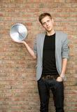 Νέος επιχειρηματίας που κρατά ένα ρολόι στο υπόβαθρο τουβλότοιχος. Στοκ Εικόνες