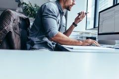 Νέος επιχειρηματίας που μιλά στο κινητό τηλέφωνο και που χρησιμοποιεί τον υπολογιστή Στοκ εικόνα με δικαίωμα ελεύθερης χρήσης