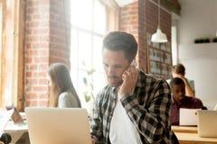 Νέος επιχειρηματίας που μιλά στο κινητό τηλέφωνο μπροστά από το lap-top Στοκ Εικόνες