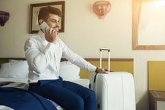 Νέος επιχειρηματίας που μιλά στο τηλέφωνο καθμένος στο δωμάτιο ξενοδοχείου Στοκ φωτογραφίες με δικαίωμα ελεύθερης χρήσης