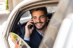 Νέος επιχειρηματίας που μιλά στο τηλέφωνο στη λιμουζίνα Στοκ φωτογραφίες με δικαίωμα ελεύθερης χρήσης
