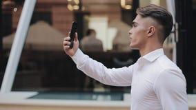Νέος επιχειρηματίας που μιλά στο smartphone που διοργανώνει την τηλεοπτική επιχειρησιακή συνεδρίαση συνομιλίας Χαμογελώντας επιχε απόθεμα βίντεο