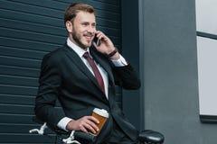 Νέος επιχειρηματίας που μιλά στον καφέ smartphone και κατανάλωσης καθμένος στο ποδήλατο Στοκ Εικόνες